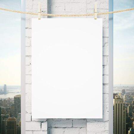 pegs: Blank poster hanging outside on rope with pegs. White brick column and city view in the background. Mock up, 3D Rendering Stock Photo