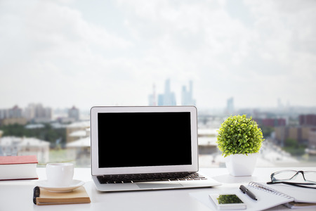 Creative windowsill workplace with blank laptop computer, decorative plant, smartphone, glasses, several notepads, pen, book and coffee cup on blurry city background. Mock up
