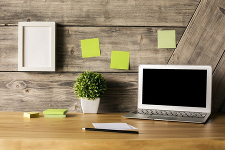 white poster: Closeup of creative wooden designer desktop with blank laptop screen, picture frame, plant and stationery items. Mock up