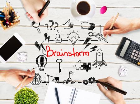 articulos oficina: Concepto de Brainstorm con manos de empresarios bosquejo de dibujo en escritorio de oficina de madera ligero con smartphone en blanco, taza de café, papelería y otros elementos