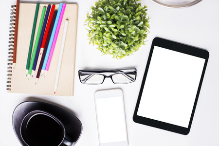 cofee cup: Top view of light office desktop with blank white tablet, mobile phone, cofee cup, glasses, plant and stationery items. Mock up