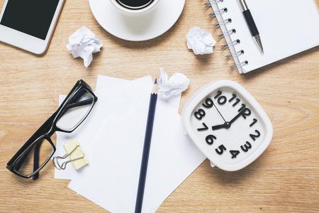 ball pens stationery: lugar de trabajo desordenado con el papeleo, reloj, gafas, teléfonos inteligentes, taza de café y artículos de papelería