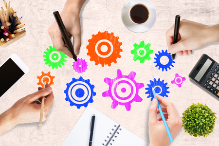 wooden work: Team work concept with hands drawing abstract colorful cogwheels on wooden office desktop with blank smartphone, coffee cup, stationery items, calculator and decorative plant