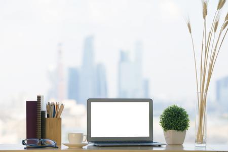 Primo piano del posto di lavoro creativo designer con computer portatile bianco in bianco, piante decorative, articoli di cancelleria, libro, occhiali e tazza di caffè su priorità bassa confusa della città. Modello