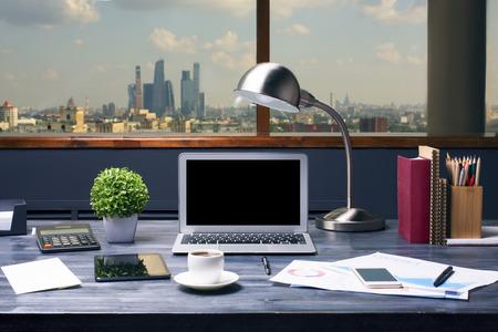 空白のラップトップ コンピューター、テーブル ランプ、植物、コーヒー カップ、タブレット、携帯電話、電卓、事業報告書、文房具と都市背景の 写真素材