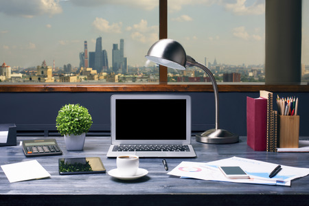 Creative designer desktop with blank laptop computer, table lamp, plant, coffee cup, tablet, cellphone, calculator, business report, stationery and other items on city background. Mock up