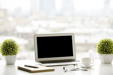 windowsill: Creative windowsill workplace with blank laptop computer, decorative plants, coffee cup, spiral notepad with pen and glasses on blurry city background. Mock up