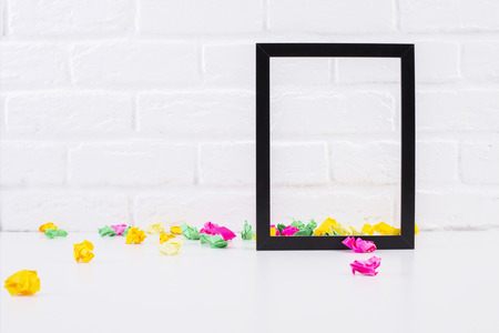 decor: Empty see-through picture frame and colorful crumpled paper pieces on white brick background. Mock up Stock Photo