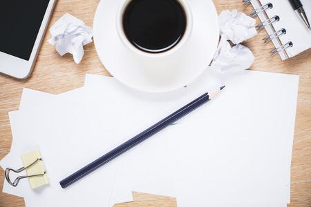 oficina desordenada: Messy office desktop with paperwork, coffee cup and smartphone Foto de archivo