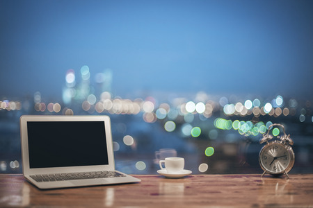 windowsill: Front view of creative designer desktop with blank laptop, silver alarm clock and coffee cup on blurry night city background. Mock up