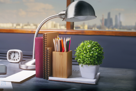 Closeup of table lamp, notepads, book, pencil holder, clock and plant on dark wooden office desktop. Window with city view in the background