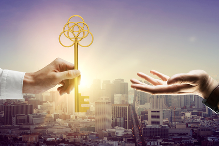 Man handing big golden key to another person on city background with sunlight Stock Photo