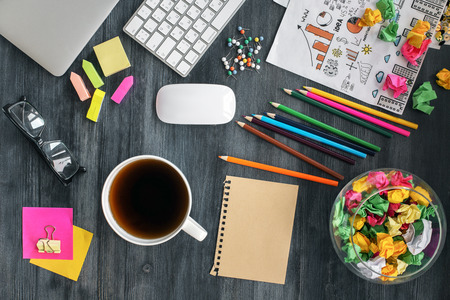 office supplies: Top view of messy office desktop with blank brown paper sheet, coffeetea mug, glasses, keyboard, closed laptop, business sketch and colorful supplies. Mock up Stock Photo