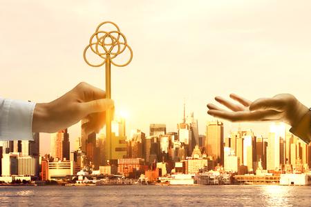 Businessperson uitdelen grote gouden sleutel aan een andere man op de achtergrond van de stad met zonlicht