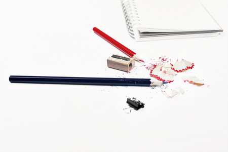 filings: Closeup of white desktop with pencils, sharpener, sawdust, small peg and spiral notepad Stock Photo