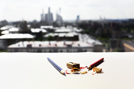 filings: White surface with pencils, sharpener and sawdust on blurry city background Stock Photo