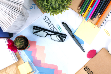 oficina desordenada: Top view and closeup of messy office desktop with glasses, business report, cactus, open book and stationery items