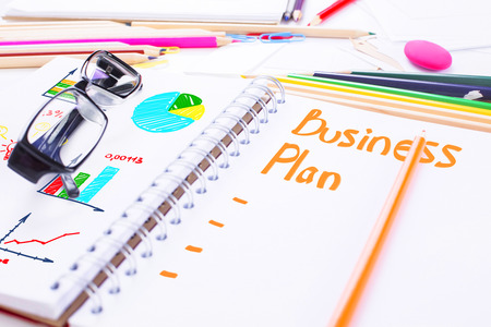 Closeup of spiral notepad with unfinished business plan and business charts, surrounded with stationery items