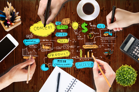 office desktop: Success concept with businesspeople hands drawing sketch on wooden office desktop with blank smartphone, coffee cup, stationery and other items