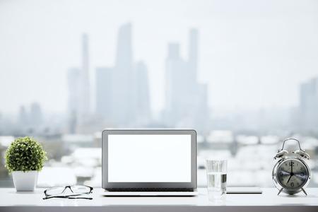 Primo piano del computer portatile bianco in bianco sul davanzale con un bicchiere d'acqua, sveglia, occhiali, pianta decorativa e altri oggetti su priorità bassa confusa della città. Modello