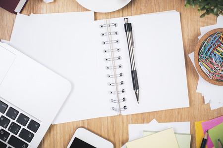 oficina desordenada: escritorio de oficina desordenada, con cuaderno de espiral, teclado, teléfono inteligente, materiales de construcción y otros artículos