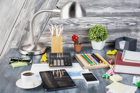 articulos oficina: Primer plano de escritorio desordenado creativa con la tablilla en blanco, teléfono inteligente, calculadora, lámpara de mesa, plantas decorativas, vasos, diversos artículos de papelería y otros objetos en el fondo de madera del tablón. Bosquejo Foto de archivo