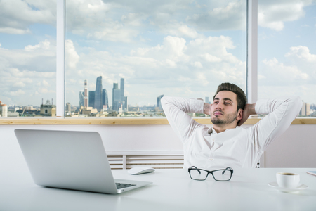 hands on head: Young european businessman relaxing in modern bright office room with city view Stock Photo