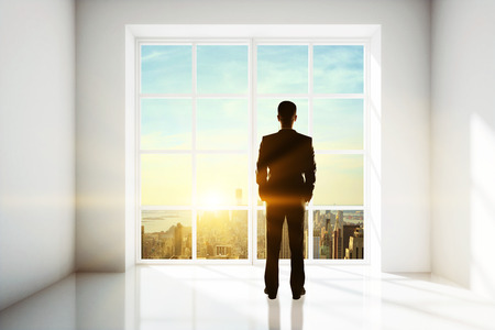 Businessman looking out of window in bright interior with city view and sunlight. Research concept