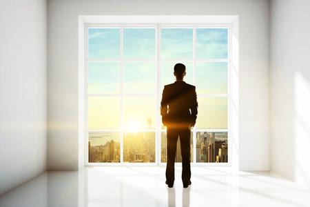 Uomo d'affari che guarda fuori dalla finestra negli interni luminosi con la vista della città e la luce del sole. Concetto di ricerca