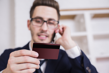 placing: Blurry businessman in office placing an order by mobile phone Stock Photo