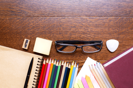 Top view of dark wooden office desktop with glasses, spiral notepad, book, colorful pencils, stickers, eraser and sharpener. Mock up