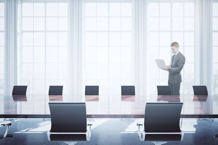 white window: Young businessman using laptop in bright conference room interior with daylight. 3D Rendering