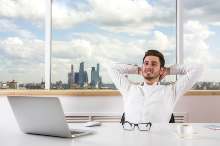 laptop computer: Handsome young businessman relaxing in modern bright office room with city view