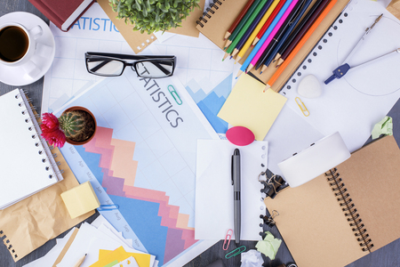 stationery items: Top view of messy creative desktop with business report, clock, glasses, coffee cup and variety of colorful stationery items