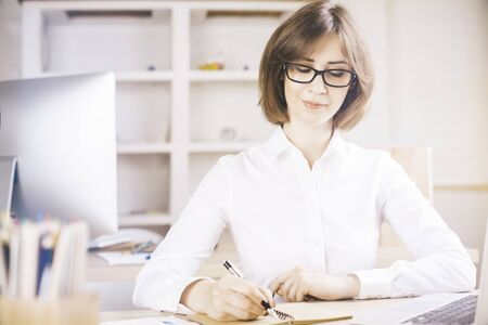 modern businesswoman: Friendly young businesswoman doing paperwork in modern office with daylight
