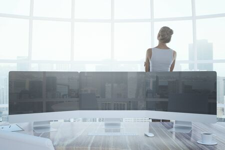 pc: Thoughtful businesswoman in office interior with three computer monitors put together as a digital panel, coffee cup and other items. Windows with city view in the background. Mock up, 3D Rendering