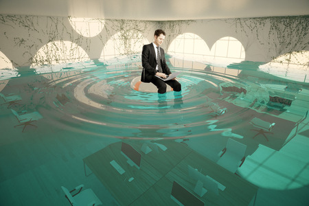 Businessman with laptop sitting on lifebuoy in abstract flooded office interior. 3D Rendering Foto de archivo