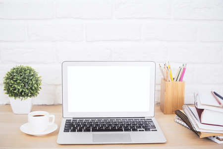 Closeup of creative hipster desktop with blank white laptop, coffee cup and other stationery and decorative items on brick background. Mock up Stockfoto
