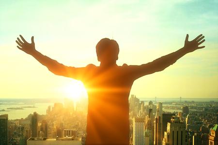 iluminado a contraluz: silueta de hombre de negocios que celebra éxito en la ciudad de fondo con la luz del sol Foto de archivo