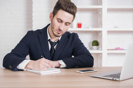Businessman writing in notepad at wooden office table with laptop ans smartphone Stock Photo