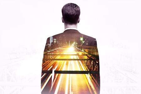 Businessman looking at illuminated city road on light background. Double exposure Stock Photo