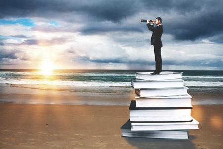 research: Hombre de negocios con los prismáticos que se coloca en la pila libro de resúmenes en la playa con la puesta del sol. La educación y la investigación concepto