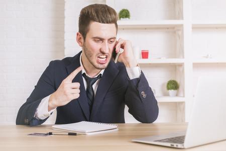 enfado: Mad empresario hablando por teléfono en su escritorio de oficina con ordenador portátil, bloc de notas y otros itmes Foto de archivo