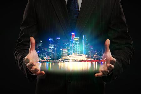 man holding transparent: Businessman in suit holding city hologram on dark background