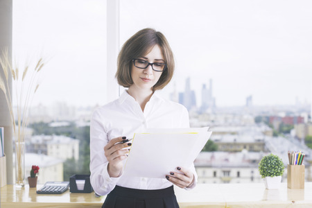 modern businesswoman: Focused businesswoman doing paperwork in modern office with city view