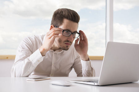 closely: Portrait of young office worker looking closely at laptop screen Stock Photo