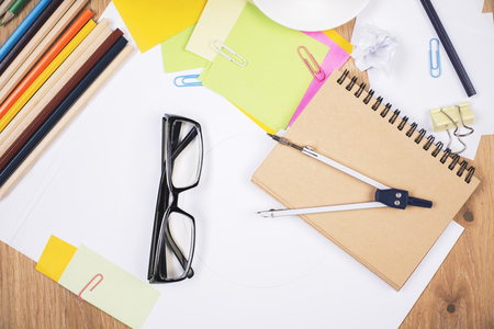 stationery items: Closeup of wooden office desktop with glasses, colorful pencils, pair of compasses and other stationery items