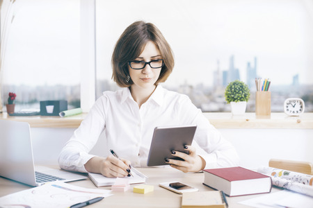 working attire: Attractive businesswoman using tablet at messy office desktop with various items
