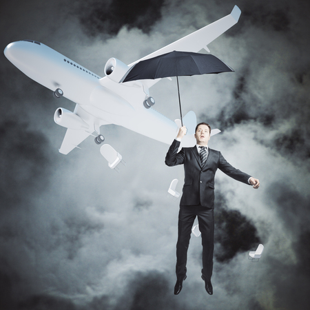 Man with umbrella falling out of airplane on night sky background