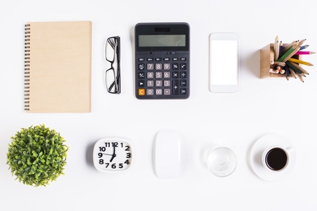 Top view of light office desktop with blank spiral notepad, glasses, white smartphone, calculator, decorative plant, coffee cup, computer mouse, pencils, clock and water glass. Mock up Stock Photo